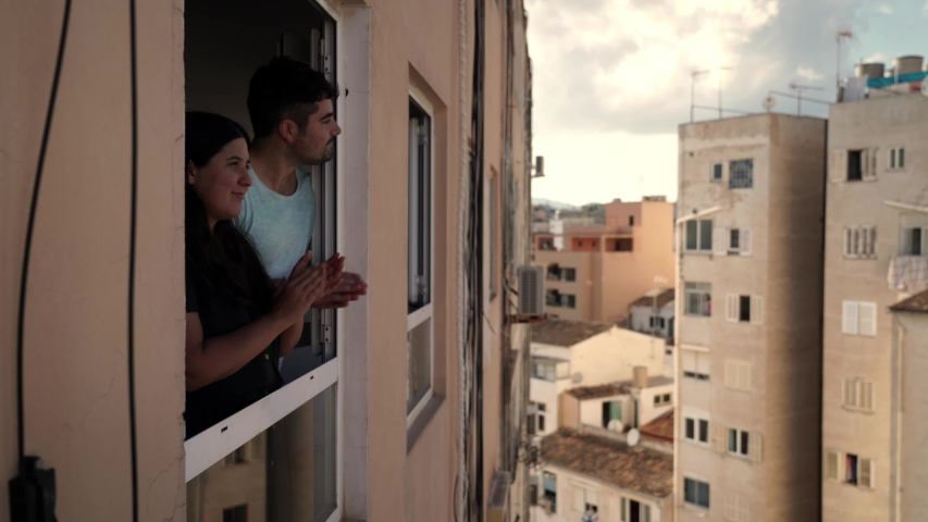 Young spanish couple giving an applause to all sanitary staff and kissing from her apartment window during quarantine from COVID 19 in Mallorca, Spain   Shutterstock HD Video #1052731235