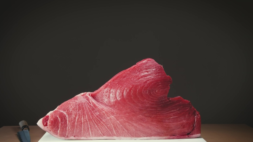 Large piece of red bluefin tuna flesh placed on table near knife in Asian restaurant   Shutterstock HD Video #1052731382
