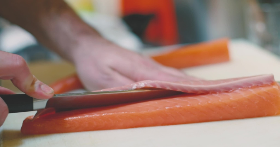 Zoom out view of anonymous cook slicing raw salmon flesh while preparing sushi in traditional Japanese restaurant   Shutterstock HD Video #1052731409