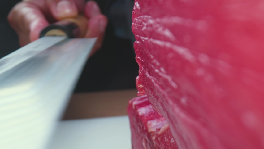 Zoom out view of anonymous cook slicing raw bluefin tuna flesh while preparing sashimi in traditional Japanese restaurant   Shutterstock HD Video #1052731421