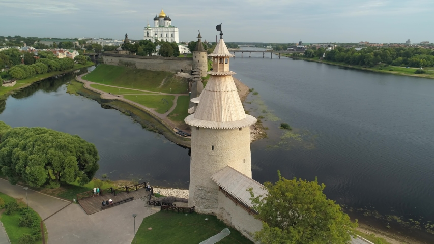 Epic Pskov region Kremlin medieval stone fortress wall ancient towers fortress stronghold. Historic Russia Trinity Cathedral Castle surrounded moat by river. Dramatic clouds cityscape. Aerial sideways