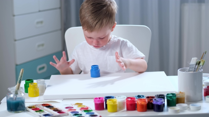 Blond Caucasian boy in bright children's room in white t-shirt paints his hands with blue hand paint and puts handprints on canvas, kids is engaged in artistic art by drawing with his hands on paper. | Shutterstock HD Video #1052735411