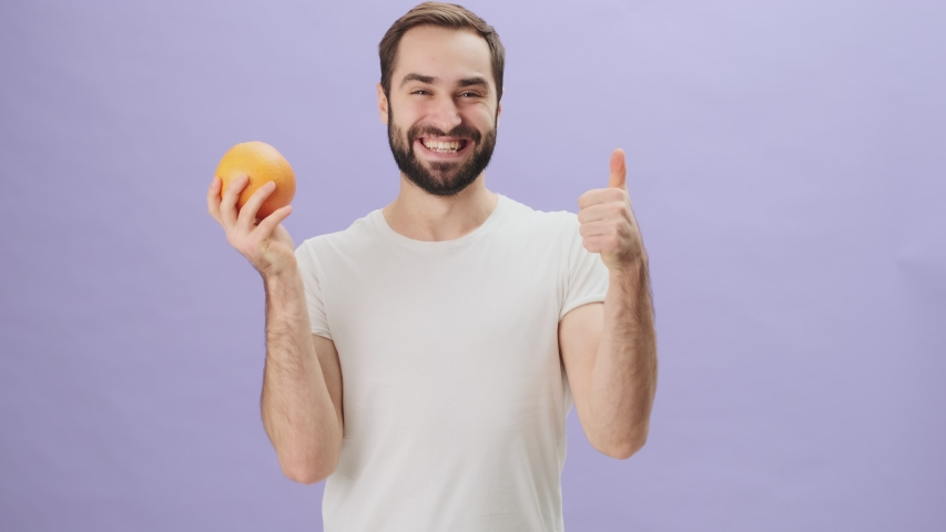 A happy young man wearing a white t-shirt is showing an orange and making a thumb-up gesture standing isolated over gray background