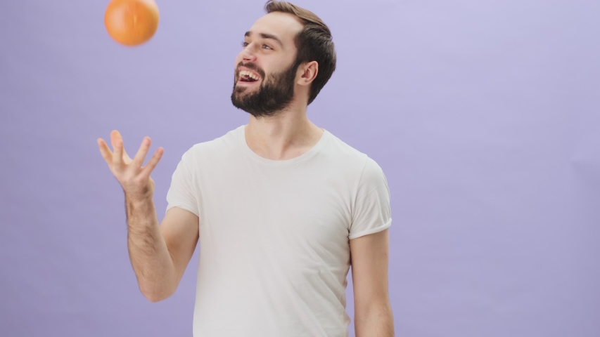 A positive smiling young man wearing a white t-shirt is throwing up an orange and making a thumb-up gesture standing isolated over gray background