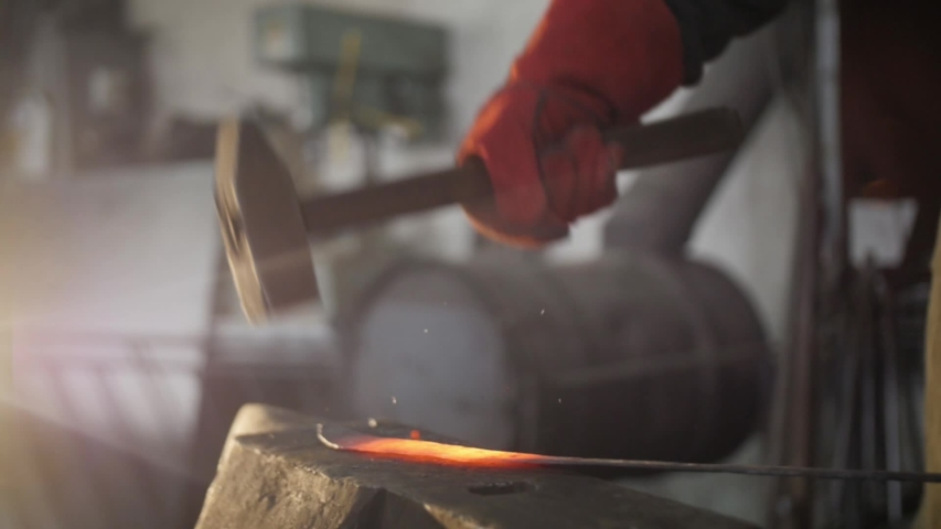 Blacksmith make a sword on anvil with a hammer. Slow motion.  | Shutterstock HD Video #1052741594