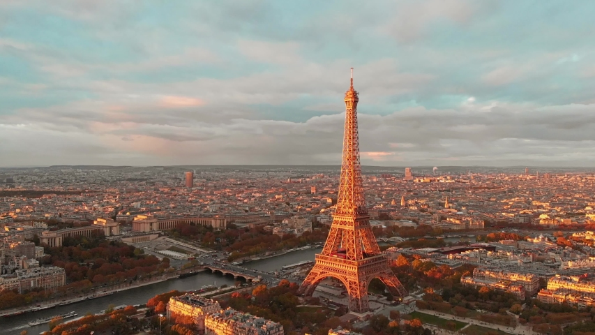 Aerial drone distant sunset view of Tour Eiffel Tower and Seine River bridge traffic cars driving, Paris city attractions, France