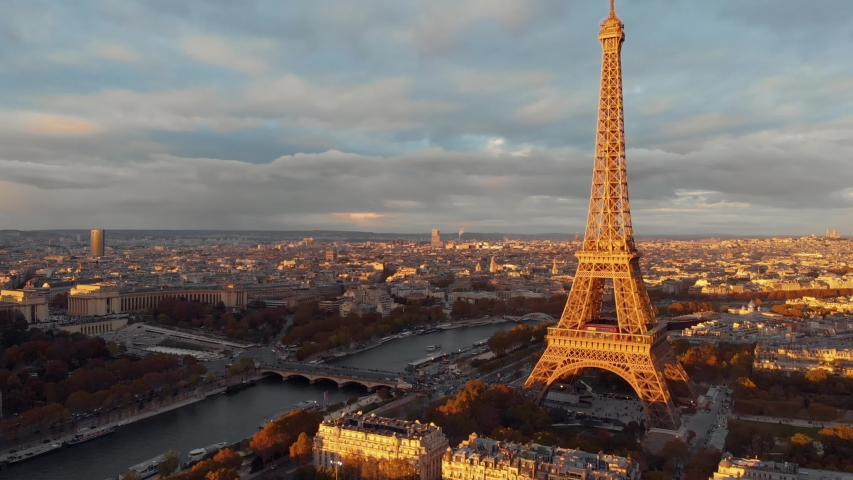 Aerial drone distant sunset view of Tour Eiffel Tower and Seine River bridge traffic cars driving, Paris city attractions, France  Royalty-Free Stock Footage #1052743418