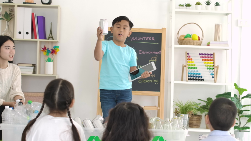 Schoolboy standing in front of the class and presenting about recycling to his Elementary Class. Kindergarten pre school concept.