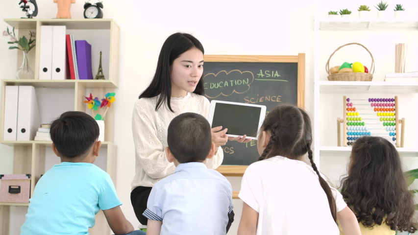Young asian female teacher teaching school kids on digital tablet in classroom at school