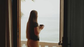 Alone woman is drinking coffee or tea in morning on balcony with blue sea view, point of view from window, rapid video, slow motion, 4k