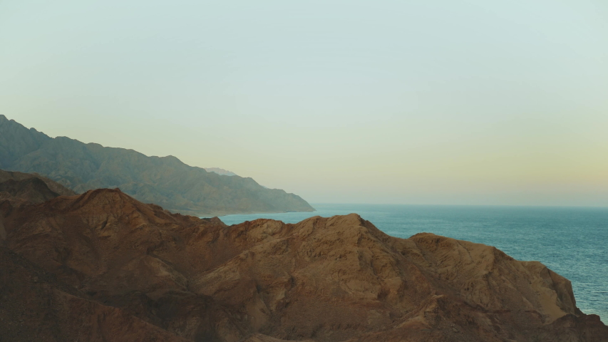 Amazing sunset at Egypt Sinai mountains and blue sea on horizon, mountains peaks, slow motion, 4k