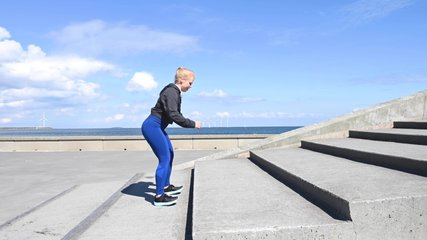 Attractive young Scandinavian, Caucasian woman, jumping up and down as exercise. The camera is looking up at her. It's a beautiful sunny day with blue sky and some clouds. Stock footage video