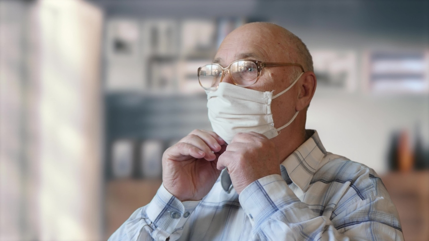 Concept of health and safety of old people during the pandemic of the coronavirus COVID-19. Elderly man with glasses dressing up a handmade homemade protective mask indoors | Shutterstock HD Video #1052755691
