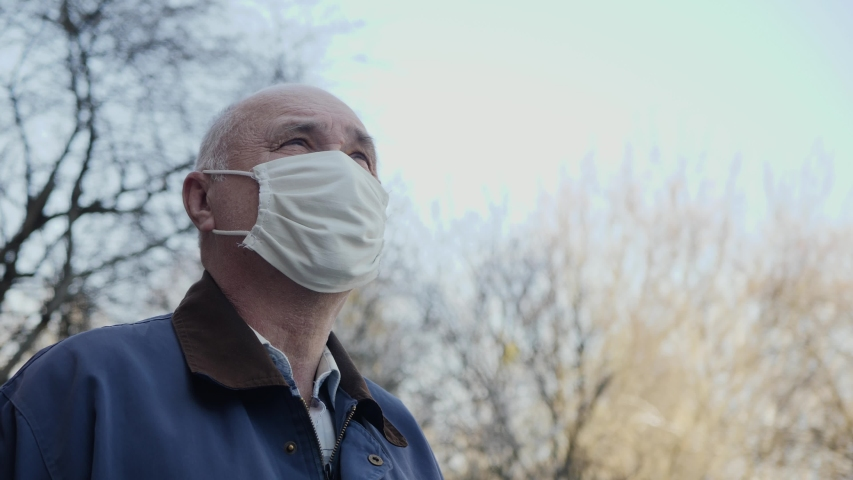 Portrait of elderly man with handmade mask on his face to protect himself from coronavirus pandemic. Close-up of man standing outdoors looking up at the sky. Concept of hope, faith, health and safety | Shutterstock HD Video #1052755694