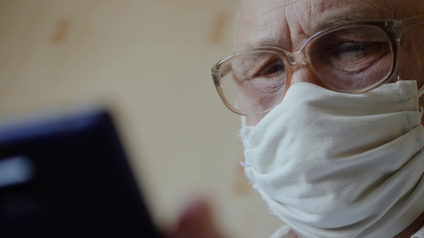 Sad elderly man in isolation at home wearing a handmade virus protection mask uses phone close up. Reading news from a smartphone in a home interior. Old man with glasses stays in quarantine at home