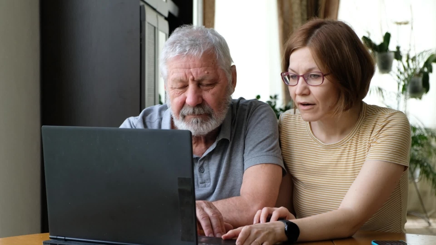 Happy senior elder father grandfather and adult grown daughter, helping him with computer