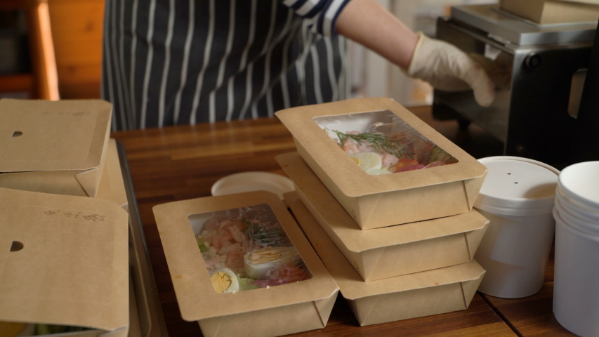 Restaurant worker wearing medical mask and gloves collecting a food box take away. Food delivery services during coronavirus pandemic and social distancing. Online contactless food shopping. Royalty-Free Stock Footage #1052759195