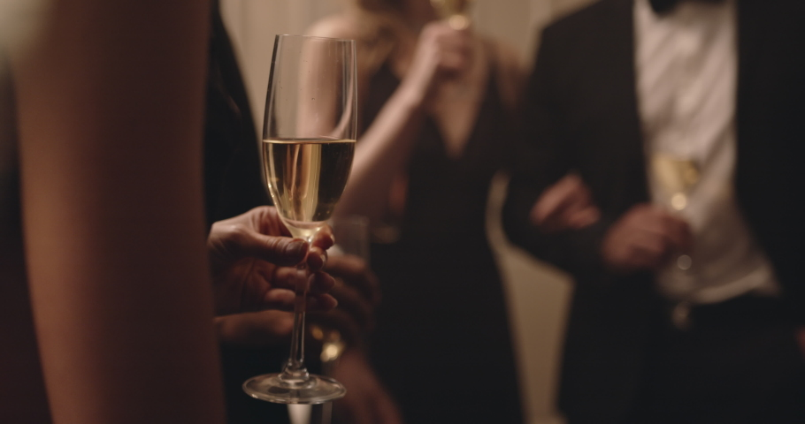Multi-ethnic friends drinking wine at a party. Group of men and women raise their glasses for a toast at new years party.  Royalty-Free Stock Footage #1052759903