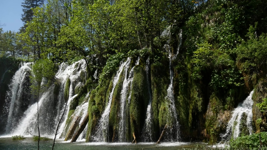 Large waterfall in the Plitvice Lakes National Park in Croatia. The Korana River, caused travertine barriers to form natural dams, which created a number of picturesque lakes, waterfalls and caves. | Shutterstock HD Video #1052761043