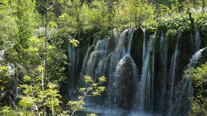 Large waterfall in the Plitvice Lakes National Park in Croatia. The Korana River, caused travertine barriers to form natural dams, which created a number of picturesque lakes, waterfalls and caves. | Shutterstock HD Video #1052761046