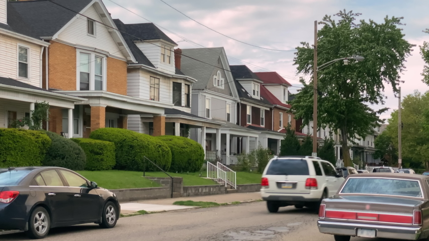 A daytime summer exterior establishing shot of typical rust belt middle class homes in a residential neighborhood of a small New England town. Pittsburgh suburbs.