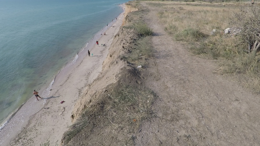 A quiet hot summer morning on the beach, a passage on the cliff, on the shore fishermen fishing | Shutterstock HD Video #1052766989