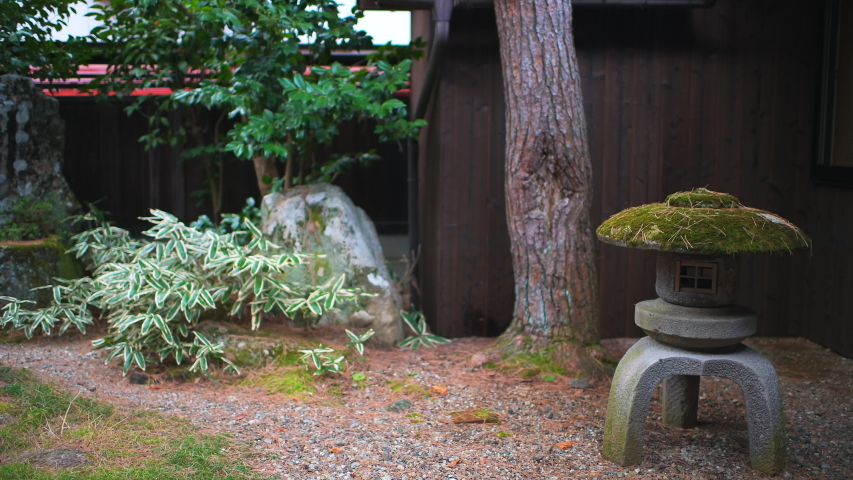 Traditional small inside indoor Japanese garden in Japan with gravel rocks and stone lantern lamp at home  | Shutterstock HD Video #1052768090