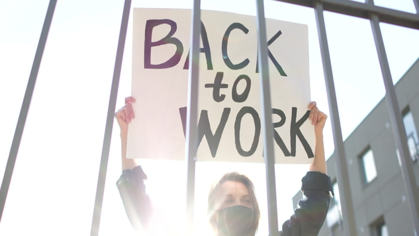 Woman in a black protective mask with a poster back to work protests against the closure of enterprises and outlets during quarantine of coronavirus covid-19. Social protests Royalty-Free Stock Footage #1052769314