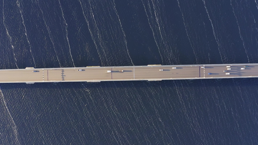 High spinning aerial overhead shot above the Tasman bridge over the Derwent river in Tasmania Australia, with traffic, cars and trucks, crossing in morning light, whites streaks on the water