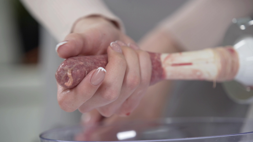 Woman cooks sausages in traditional way using sausage filler of electric mincer machine. Production of meat delicacies at home. Preparation of raw beef sausages with electric grinder. | Shutterstock HD Video #1052777816