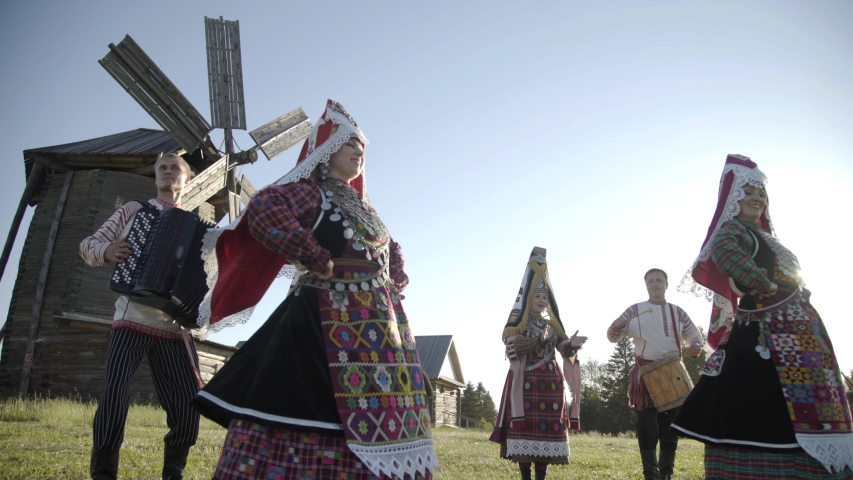 Folklore ensemble indigenous people dancing in traditional clothing outdoor on traditional antique wooden windmill background. Group of happy people wearing national Finno Ugric clothes at sunny day. Royalty-Free Stock Footage #1052777876
