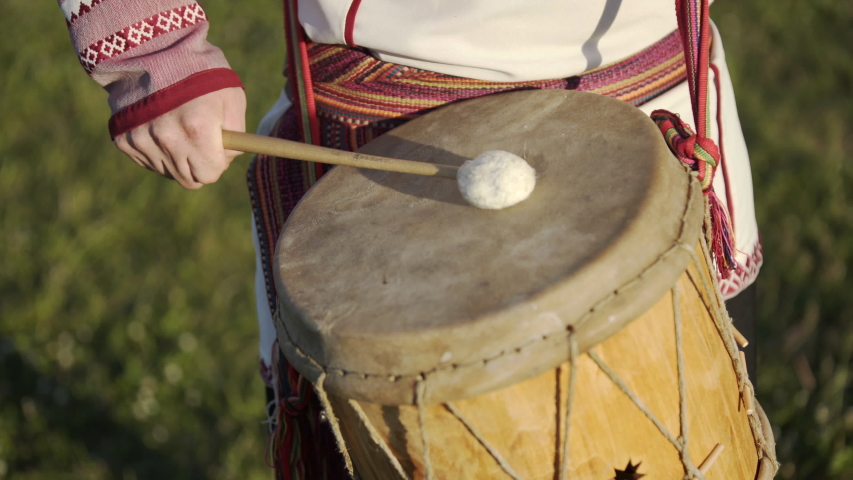 Man in traditional russian clothes dancing and playing on folklore drum outdoor on traditional antique wooden windmill background. Man wearing national Finno-Ugric clothes. Royalty-Free Stock Footage #1052777879