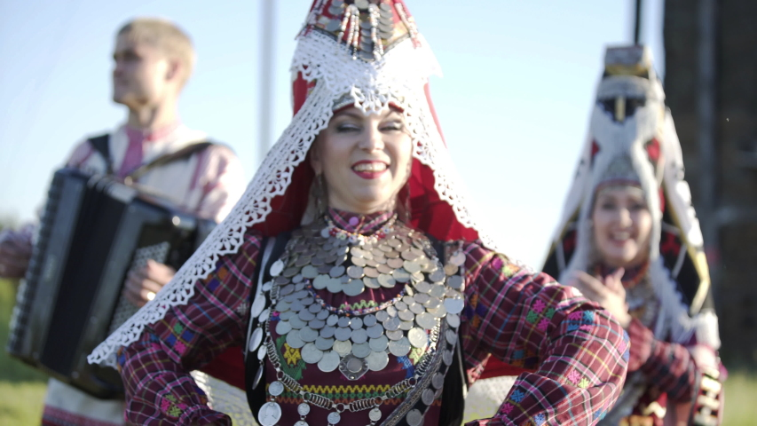 People in traditional russian clothes dancing outdoor on traditional antique wooden windmill background. Group of happy people wearing national Finno-Ugric clothes. Royalty-Free Stock Footage #1052777897