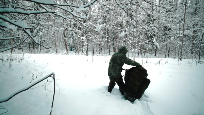 Military man in green camouflage uniform with big backpack moving through winter forest. Winter warfare and military concept. Military exercises in forest. | Shutterstock HD Video #1052777945