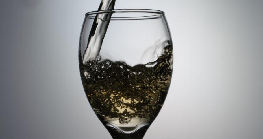 Closeup shot of glass being filled up with stream of alchoholic white wine in slow motion, pouring beverage into goblet, isolated on white background | Shutterstock HD Video #1052779616