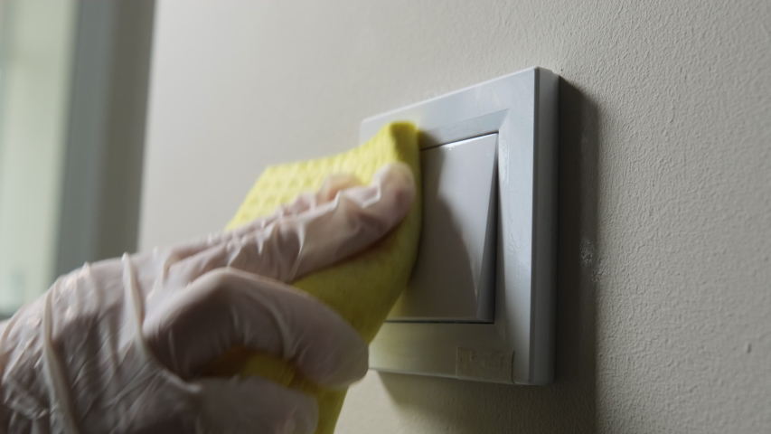 Close up view of hand wipes the surface with an anti-bacterial agent. Disinfection of the light switch in the room. Coronavirus cleaning and disinfection | Shutterstock HD Video #1052779904