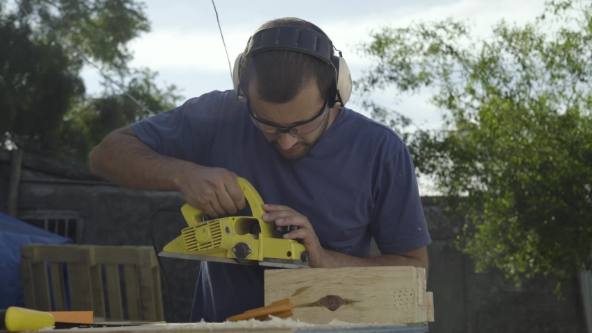 Young male woodworker using power tools to plane and sand lumber | Shutterstock HD Video #1052780096