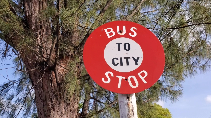 Red Bus stop sign to city with trees swaying and blue sky in beautiful Caribbean island of Barbados