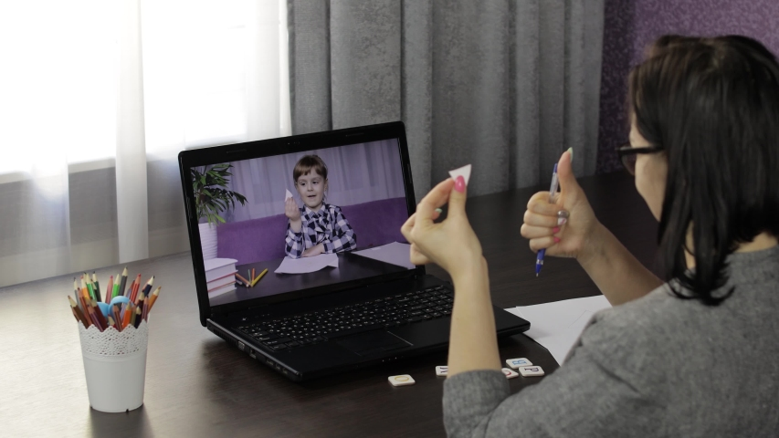 Woman teacher looking at laptop web camera making video call with little school girl pupil. Working from home. Distance education with children online class for kids on internet. Webcam e-learning