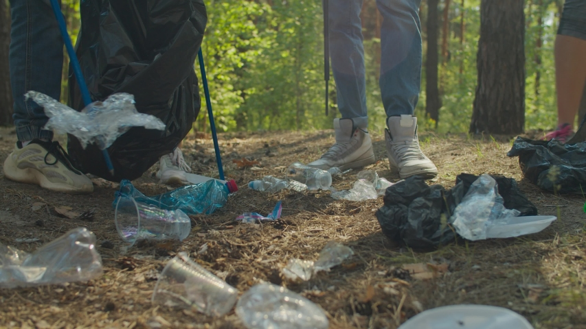 Low section of diverse young volunteers tidying up rubbish in forest using garden tools. Group of charity eco activists picking up plastic waste and garbage in woodland. Environmental awareness. | Shutterstock HD Video #1052795786