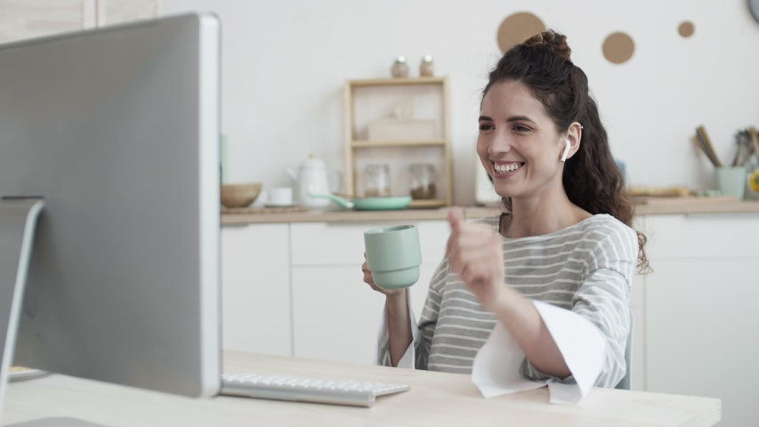Lockdown of curly-haired woman wearing wireless headphones sitting at table at PC, talking by video link and drinking tea. Then she taking plate from microwave and continuing chat   Shutterstock HD Video #1052799431
