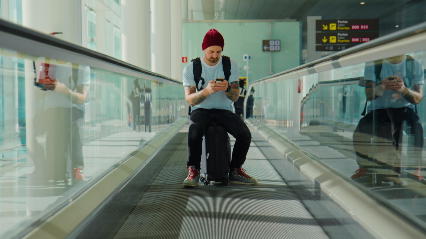 Cool and modern looking young hipster man, sit on suitcase in empty airport terminal. Look at smartphone for online boarding pass or cancelled departures, arrivals flights. Urban nomad travel blogger