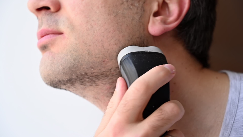 Man shaving with an electrical shave leaving irritated red skin, slow motion | Shutterstock HD Video #1052804225