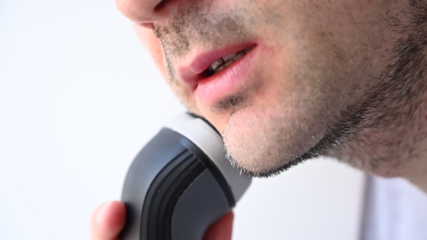 Man shaving with an electrical shave leaving irritated red skin, slow motion | Shutterstock HD Video #1052805500