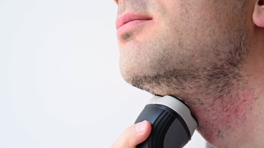 Man shaving with an electrical shave leaving irritated red skin, slow motion | Shutterstock HD Video #1052805506