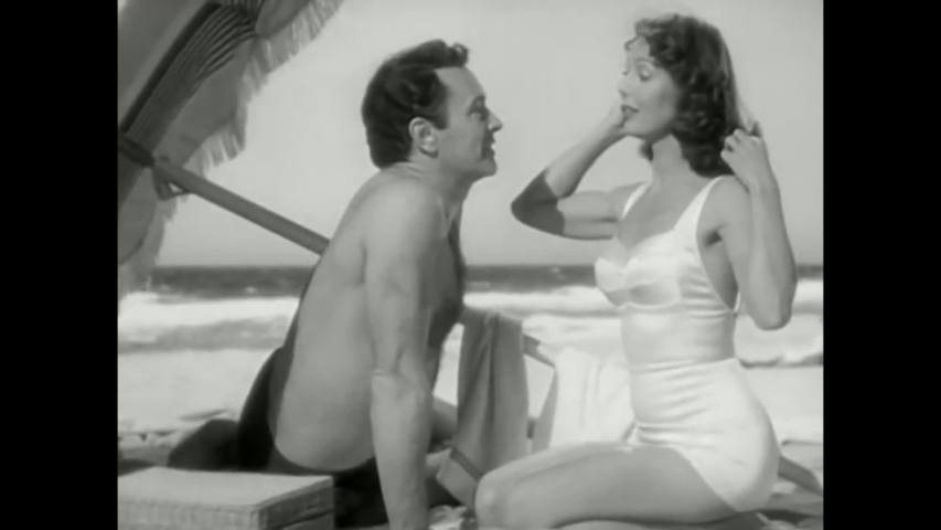 CIRCA 1951 - A man and woman (Loretta Young) flirt as they open a picnic basket on the beach in a classic Hollywood drama.