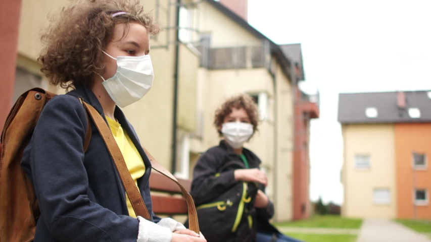Schoolchildren, a masked boy and girl are sitting on a bench near the school at a safe distance. Social distance, new teaching rules, back to school after quarantine Royalty-Free Stock Footage #1052809889