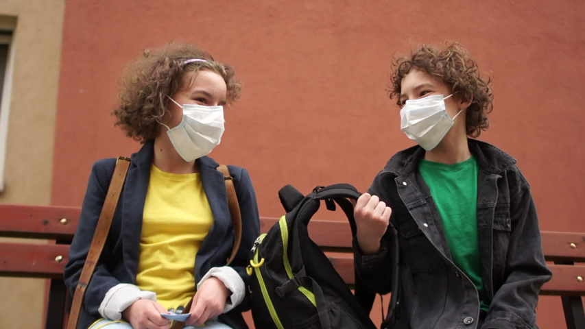 Cute curly boy and girl are sitting on a bench at a safe distance and talking. Back to school after quarantine Royalty-Free Stock Footage #1052809892