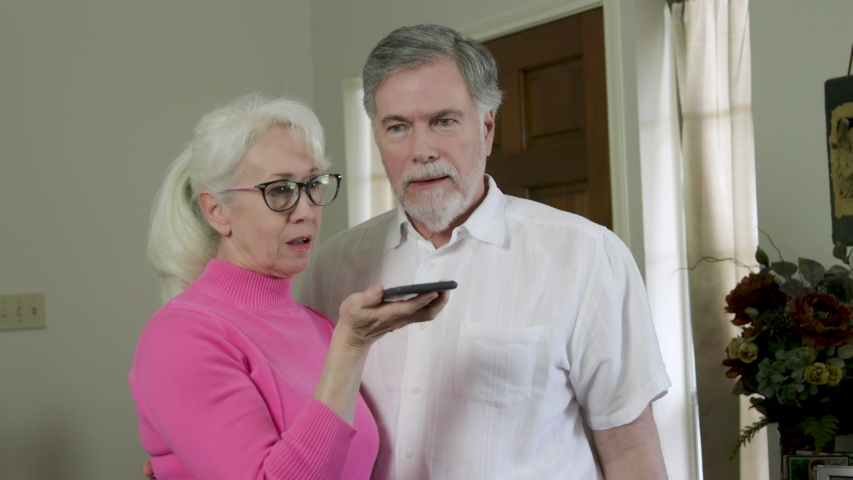 An older couple standing in their living room talking on a conference call via a smart phone that makes them celebrate with a hi five and a hug when done.