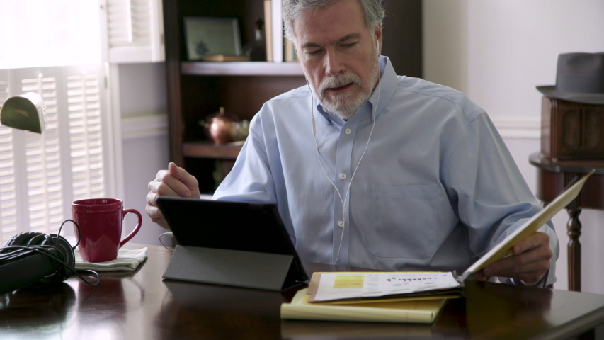 A team leader in his living room holding a video meeting via his tablet pc with team members collaborating virtually due to the pandemic and the new reality in 2020 of working from home. Royalty-Free Stock Footage #1052811314
